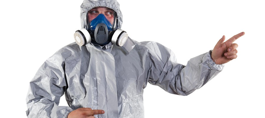 A pest control worker wearing a mask, hood, protective suit and